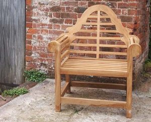 Wooden garden chair in front of brick wall