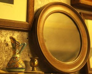 round antique mirror next to an ornamental jug and brass candle stick
