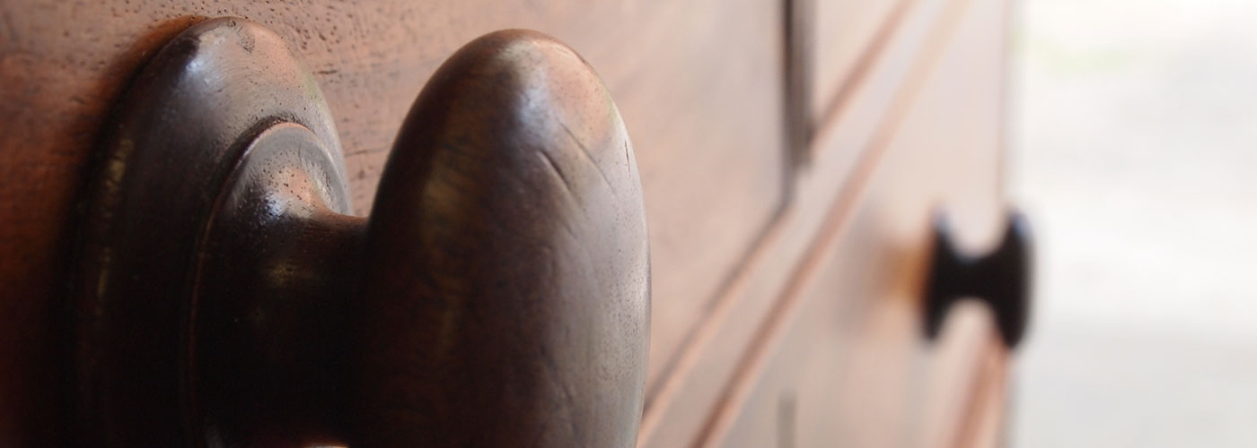 Close up of antique wood chest of drawers knob handle